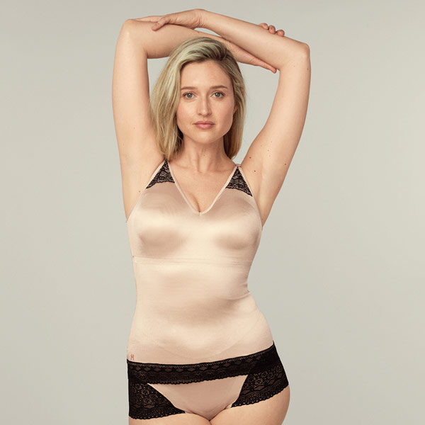 Woman modeling a Ruby Ribbon nude and black lace cami, looking very comfortable
